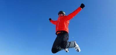 Uomo vestito da sci che salta
