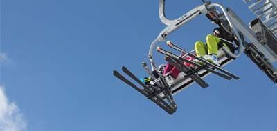 People in the chairlift on the Tarvisio with equipment from Lussari sports