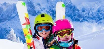 Happy kids with ski equipment rented from Lussari Sport