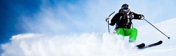 Skier in fresh snow with Lussari sport ski equipment