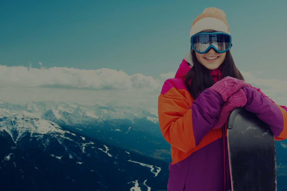 Ragazza felice con snowboard noleggiato da Lussari sport